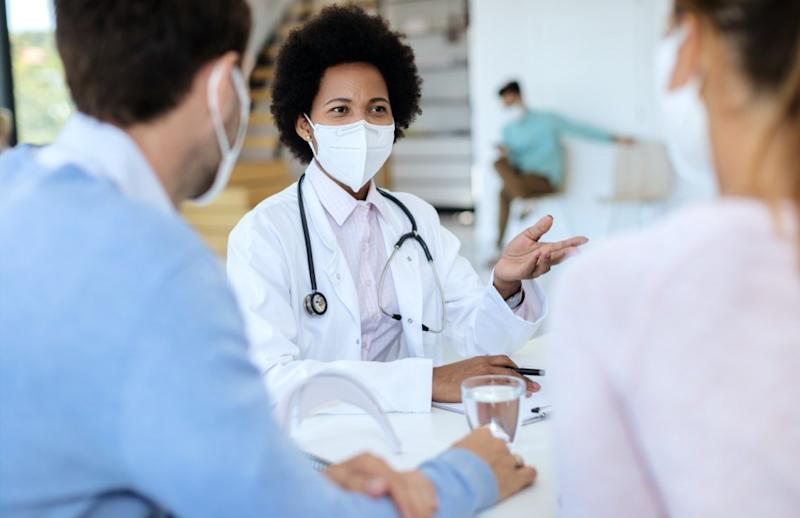 doctor wearing protective face mask while talking to her patients during an appointment