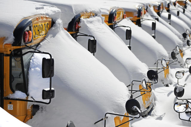 School buses are covered in snow after a winter storm in Hartford, Conn., Sunday, Feb. 10, 2013. A howling storm across the Northeast left much of the New York-to-Boston corridor covered with more than three feet of snow on Friday into Saturday morning. (AP Photo/Jessica Hill)