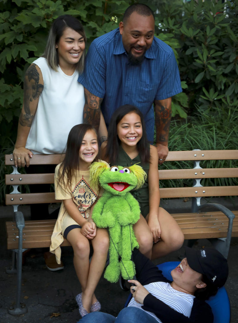 """This Aug. 6, 2019 photo shows Jaana, standing left, and Sam Woodbury, from Irvine, Cali., and their daughters Salia, 10, seated right, and Kya, 6, with """"Sesame Street"""" muppet Karli and puppeteer Haley Jenkins in New York. Salia, whose parents are in recovery, is featured with Karli in a segment about addiction. The initiative is part of the Sesame Street in Communities resources available online. (AP Photo/Bebeto Matthews)"""