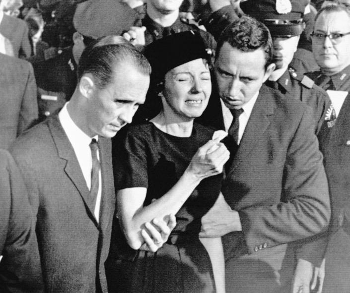 FILE - In this Monday, Nov. 25, 1963, file photo, Marie Tippit, widow of police officer J.D. Tippit who was slain during the search for President John F. Kennedy's assassin, is led weeping from Beckley Hills Baptist Church in Dallas after funeral services for her husband. Tippit who was a 35-year-old mother of three when her husband, Officer J.D. Tippit, was killed on Nov. 22, 1963, has died at age 92. Her son said she died Tuesday, March 2, 2021, at a hospital in the East Texas city of Sulphur Springs after being diagnosed with pneumonia following a positive test for COVID-19. (AP Photo, File)