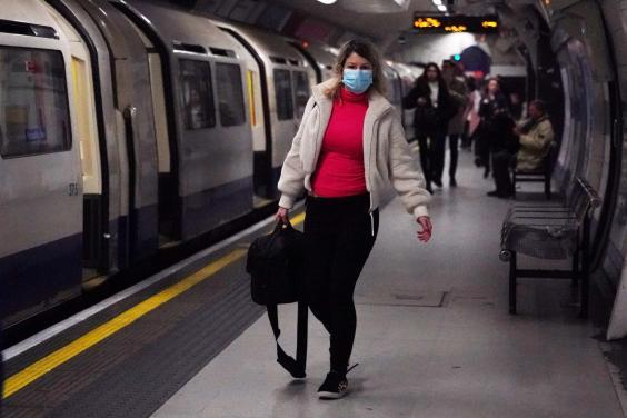 A woman wearing a protective mask walks along the platform at Leicester Square underground station in London (Reuters)
