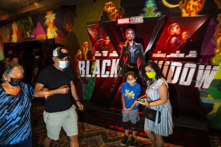 """Hollywood, CA - July 09: Masked patrons walk past a lobby display for Marvel Studios' """"Black Widow,"""" on opening weekend at the El Capitan Theatre, in the heart of Hollywood, CA, Friday, July 9, 2021. (Jay L. Clendenin / Los Angeles Times)"""