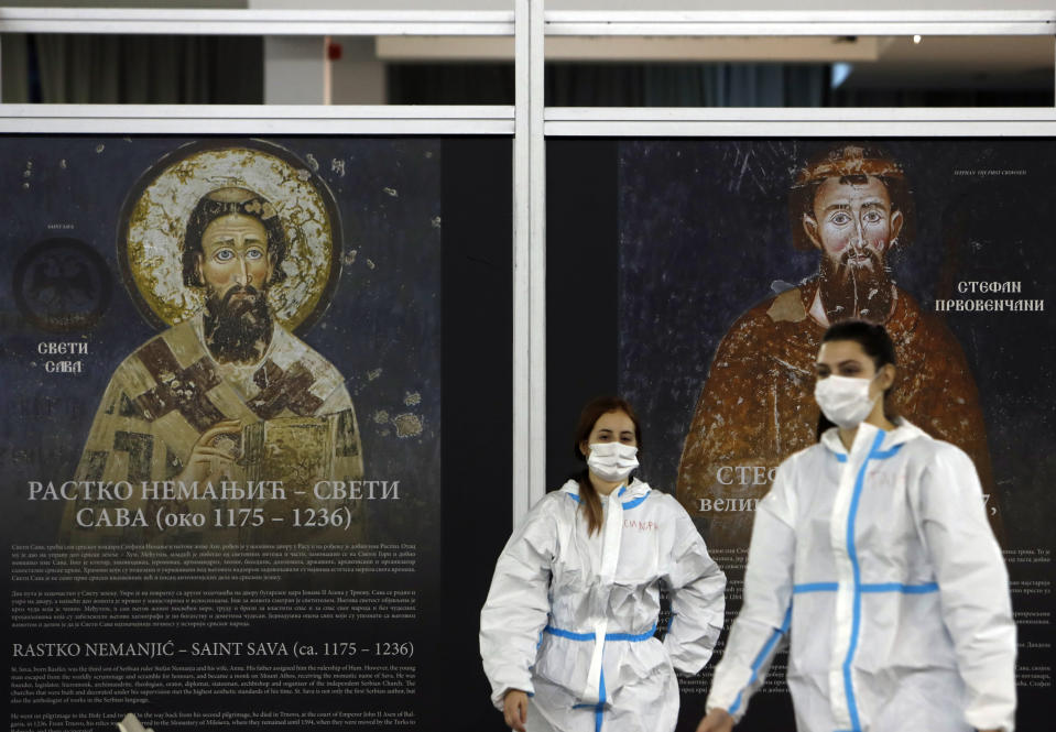 """Medical workers wearing protective gear walk at Belgrade Fair makeshift vaccination center in Belgrade, Serbia, Tuesday, Feb. 9, 2021. China is ready to consider """"vaccine cooperation"""" with Central and Eastern European countries, President Xi Jinping said Tuesday in a meeting held by video link with European leaders. Serbia has received 1 million doses of a Chinese-developed coronavirus vaccine and Hungarian and Chinese vaccine developers are cooperating. (AP Photo/Darko Vojinovic)"""