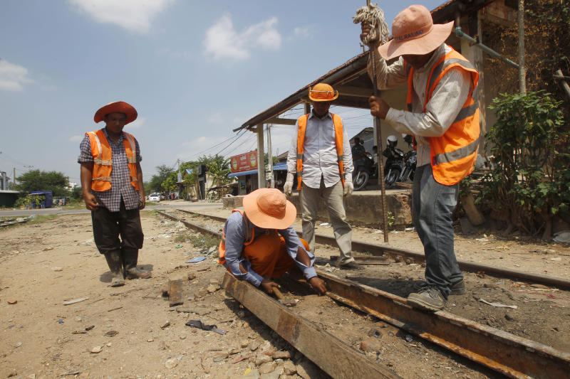 Railroad maintenance workers fix tracks outside Phnom Penh, Cambodia, Monday, April 22, 2019. The Cambodian-Thailand cross-border line has been not used for more than four decades due to Cambodia's civil war. In recent years the railroad has been renovated and both countries are looking to re-establish the rail link by the end of the year, local media say. (AP Photo/Heng Sinith)
