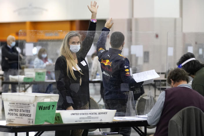 Recount observers raise hands during a Milwaukee hand recount of Presidential votes at the Wisconsin Center, Friday, Nov. 20, 2020, in Milwaukee, Wis. The recount of the presidential election in Wisconsin's two most heavily Democratic counties began Friday with President Donald Trump's campaign seeking to discard tens of thousands of absentee ballots that it alleged should not have been counted. (AP Photo/Nam Y. Huh)