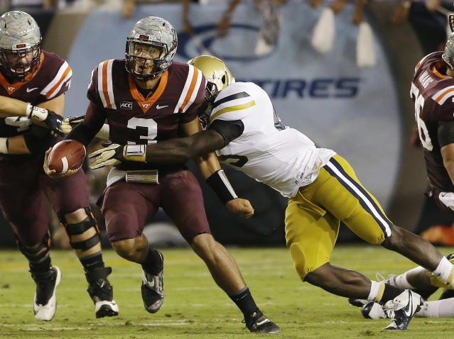 Virginia Tech quarterback Logan Thomas (3) is brought down by Georgia Tech defensive end Jeremiah Attaochu after a short gain in the first half of an NCAA college football game on Thursday, Sept. 26, 2013, in Atlanta. (AP Photo/John Bazemore)