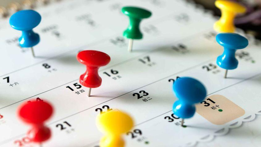 Calendar with numerous dates marked with pushpins.