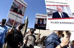 Gun owners hold signs criticizing Justin Trudeau and Bill Blair