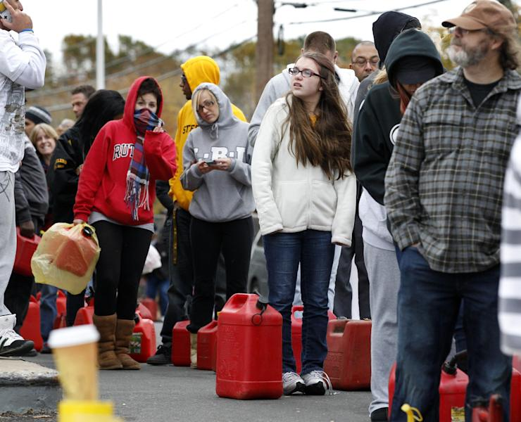 As temperatures begin to drop, people wait in line to fill containers with gas at a Shell gasoline filling station Thursday, Nov. 1, 2012, in Keyport, N.J. In parts of New York and New Jersey, drivers lined up Thursday for hours at gas stations that were struggling to stay supplied. The power outages and flooding caused by Superstorm Sandy have forced many gas stations to close and disrupted the flow of fuel from refineries to those stations that are open. (AP Photo/Mel Evans)