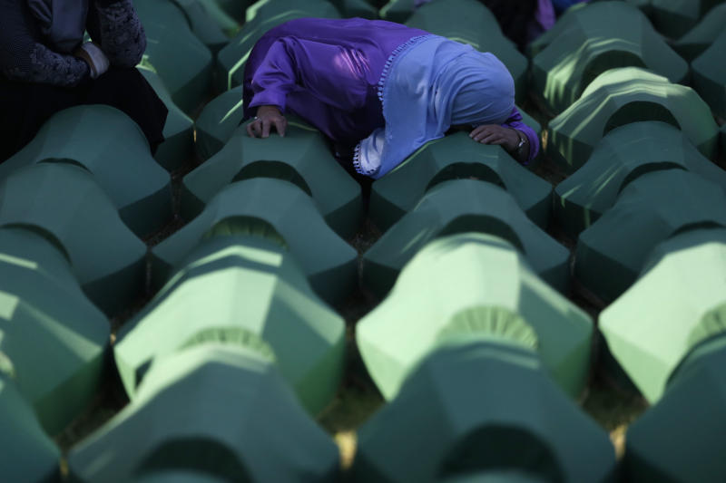 "FILE - In this Monday, July 11, 2016 file photo, a Bosnian woman prays next to a coffin containing the remains of her relative perished in the Srebrenica massacre, during a funeral ceremony for the 127 victims at the Potocari memorial complex near Srebrenica, 150 kilometers (94 miles) northeast of Sarajevo, Bosnia and Herzegovina. A Bosnian Serb leader has wrongly called the 1995 Srebrenica massacre, where over 8,000 Muslim men and boys were killed by Bosnian Serb troops, ""a fabricated myth."" Milorad Dodik, head of Bosnia's multi-ethnic joint presidency, spoke during a conference discussing war crimes. His comments defy international court rulings that said genocide was committed in the eastern Bosnian enclave and have angered Bosnian Muslims. (AP Photo/Amel Emric, File)"