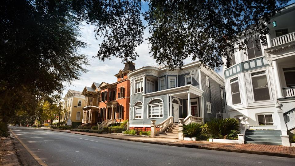 Tree lined historic homes on the community road in Savannah Georgia USA.