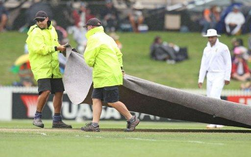 Groundstaff pull on the covers as rain falls during day one of the second cricket test match between New Zealand and South Africa, at Seddon Park in Hamilton, on March 15