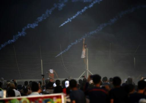 A Palestinian protester climbs a fence in Gaza as tyres burn and Israeli forces fire tear gas canisters during a demonstration along the frontier with Israel east of Gaza City on September 14, 2018