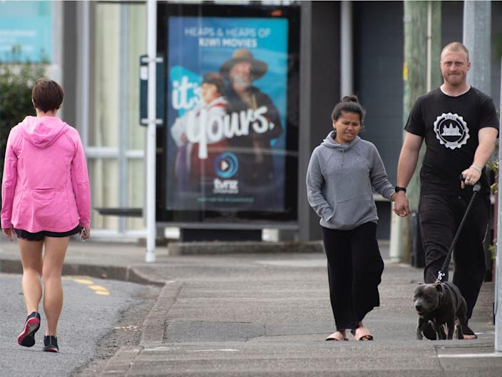 Pedestrians practise social distancing in response to the COVID-19 coronavirus outbreak along a street of Lower Hutt, near Wellington, on April 20.