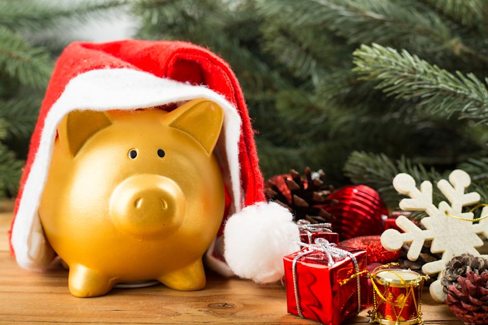 Golden Piggy bank with Santa hat under the Christmas tree.