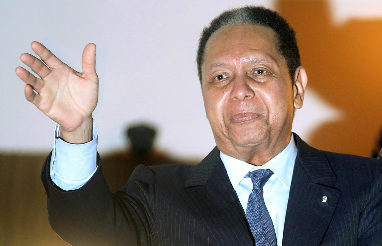 "PORT-AU-PRINCE, HAITI - JANUARY 16: (FILE PHOTO) Jean-Claude Duvalier, the former Haitian leader known as 'Baby Doc', waves to supporters from a balcony of the Hotel Karibe on January 16, 2011 in Port-au-Prince, Haiti. Accorrding to reports Haitian authorities will question former dictator Jean-Claude ""Baby Doc"" Duvalier to determine whether he should be prosecuted for stealing from the treasury during his rule January 18, 2011.   (Photo by Mario Tama/Getty Images)"