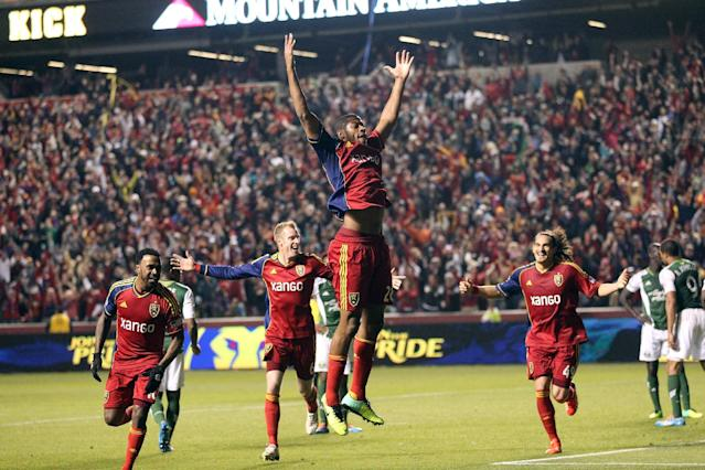 Real Salt Lake players celebrates with Chris Schuler (28) as he jumps in the air after scoring against the Portland Timbers in the first half during the first leg of the of the MLS Western Conference final Sunday, Nov. 10, 2013, in Sandy, Utah. (AP Photo/Rick Bowmer)