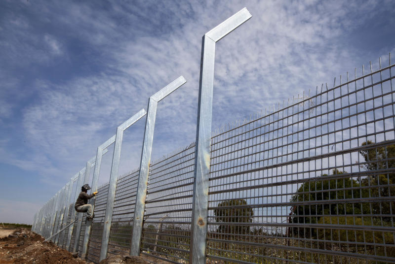 In this photo taken Wednesday, April 24, 2013, a worker builds a security fence along the border between Israel and Syrian on the Golan Heights. Against a breathtaking vista of green fields and a snowcapped mountain range, all is silent but for a strong gust of wind whipping across the landscape. The tranquility is suddenly interrupted by a burst of gunfire from beyond a newly built fortified fence: Jihadi rebels are battling with Bashar Assad's battered troops in a nearby Syrian village. Watching it all unfold are Israeli soldiers atop tanks - a sight unseen here in a generation - and the sounds of explosions from a large-scale Israeli drill are distinctly heard in the background. (AP Photo/Sebastian Scheiner)