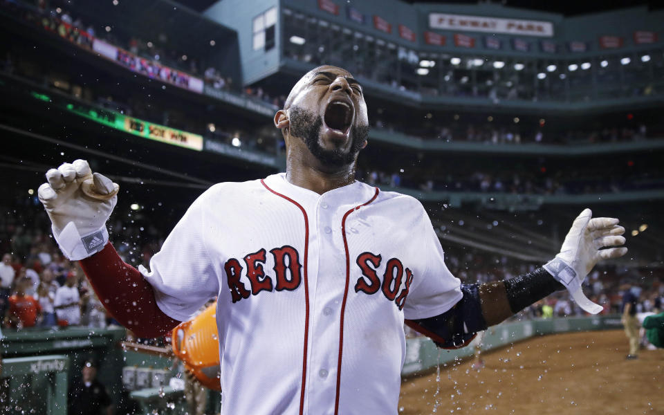 Boston Red Sox's Eduardo Nunez reacts as he is doused with water after reaching first on a throwing error, driving in J.D. Martinez and breaking a 7-7 tie, during the bottom of the ninth inning of a baseball game against the Miami Marlins at Fenway Park in Boston, Tuesday, Aug. 28, 2018. (AP Photo)