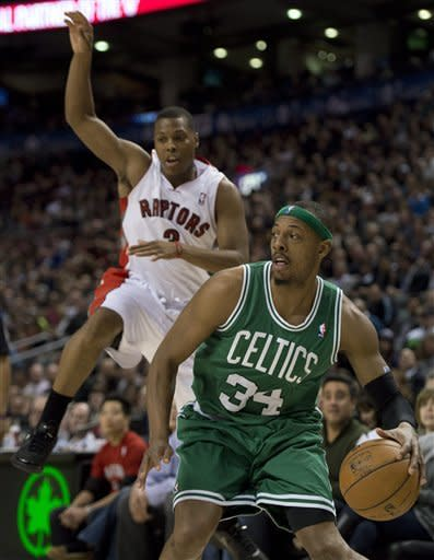 Toronto Raptors guard Kyle Lowry, left, leaps after being faked out by Boston Celtics forward Paul Pierce (34) during first-half NBA basketball game action in Toronto, Wednesday, Feb. 6, 2013. (AP Photo/The Canadian Press, Frank Gunn)