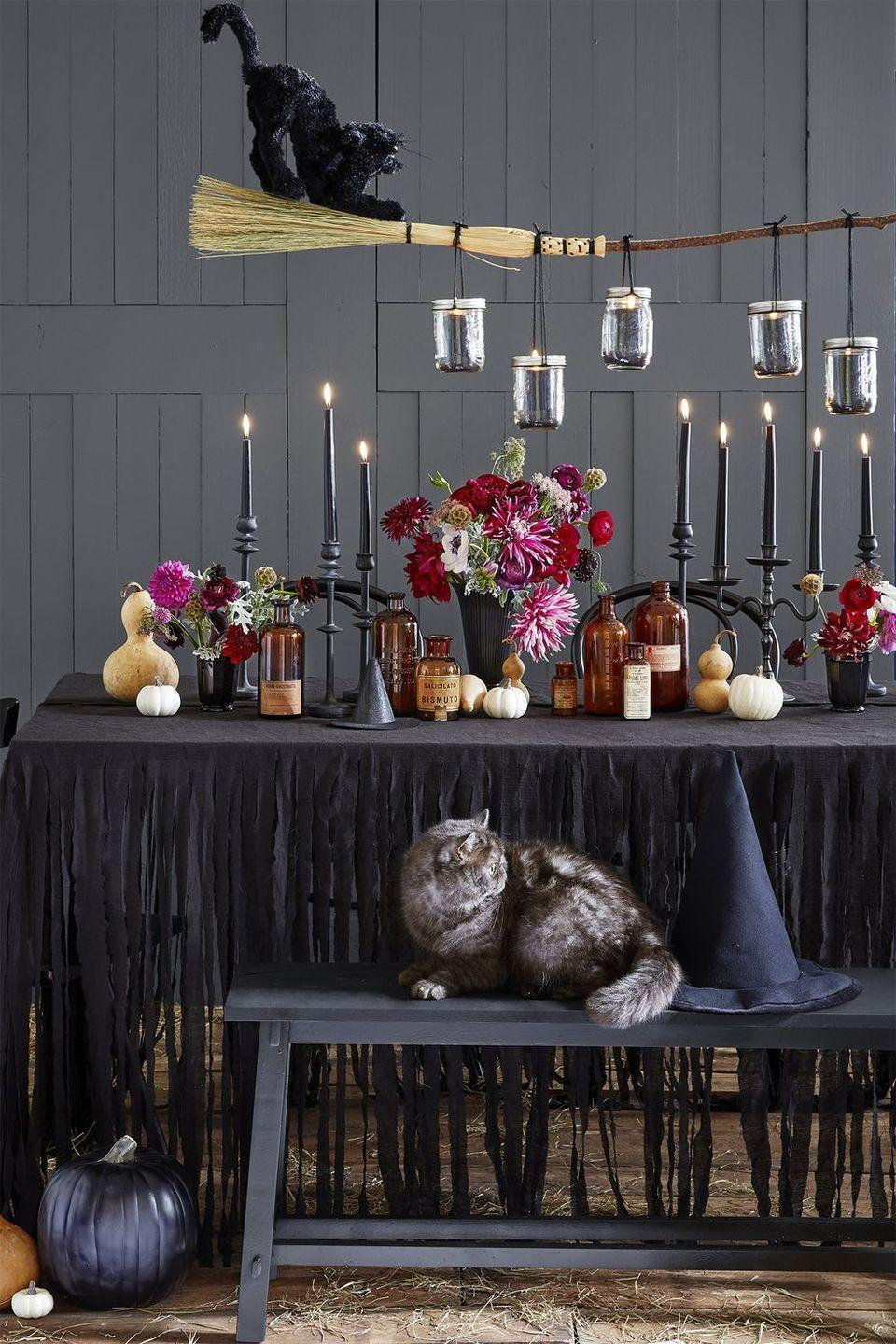 <p>Cast a spell over your dining room table by suspending a witch's broom from the ceiling. Carefully balance mason jars from the handle for added mood lighting. </p>