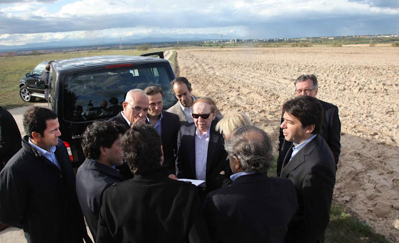 """FILE - In this photo released by the Madrid Regional Government on May 6,  2012,  CEO of Las Vegas Sands Corp. Sheldon Adelson, centre with sunglasses, talks with delegates while visiting Alcorcon on the outskirts of Madrid. Las Vegas Sands casinos and Madrid officials have chosen the town of Alcorcon on the outskirts of the Spanish capital as the site for the multi-billion dollar """"EuroVegas"""" casino project, which authorities hope will bring much needed jobs and investment to the recession-wracked country. The announcement made Friday Feb. 8, 2013 stated that the entire project, initially comprising 12 hotels and six casinos, is to be finished by 2023 at an estimated cost of euro 22 billion. Las Vegas Sands is to fund 35 percent of the project. It is not clear where the remaining 65 percent will come from. Spain has a swollen deficit and 26 percent unemployment. (AP Photo/Comunidad de Madrid, File)"""