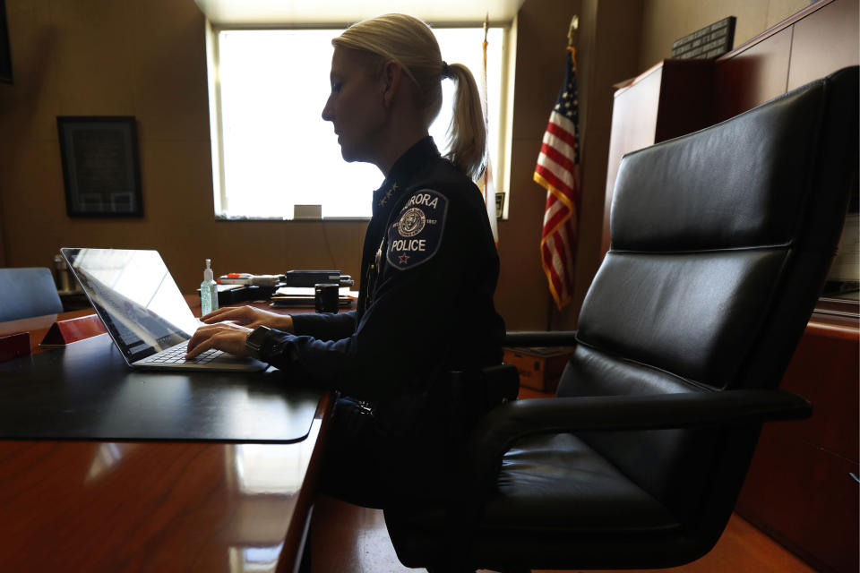 In this Monday, April 20, 2020, photo Aurora, Ill. police chief Kristen Ziman works in partial silhouette at her office in Aurora. Across the country first responders who've fallen ill and recovered, like Chief Ziman, have begun the harrowing experience of returning to jobs that put them back on the front lines of America's fight against the novel coronavirus. (AP Photo/Charles Rex Arbogast)