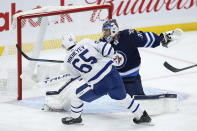 Toronto Maple Leafs' Ilya Mikheyev (65) scores on Winnipeg Jets goaltender Connor Hellebuyck (37) during the second period of an NHL hockey game Friday, May 14, 2021, in Winnipeg, Manitoba. (John Woods/The Canadian Press via AP)