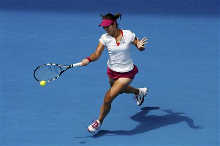 Li Na of China hits a return to Belinda Bencic of Switzerland during their women's singles match at the Australian Open 2014 tennis tournament in Melbourne January 15, 2014. REUTERS/Jason Reed