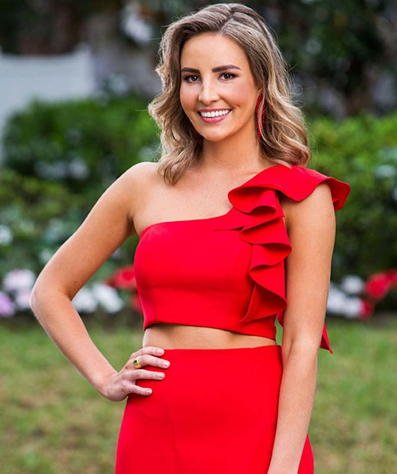 The Bachelor Australia 2019 contestant Kristen Czyszek stands in a red crop top and red skirt with a hand on her hip