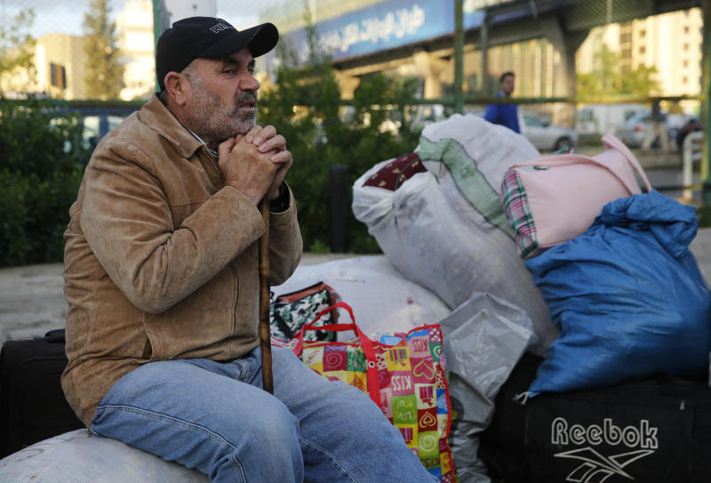 A Syrian refugee sits next to his belongings as he waits to board a bus to take him home to Syria, in Beirut, Lebanon, Tuesday, Dec. 3, 2019. Hundreds of Syrian refugees have headed home in the first batch to leave Lebanon since protests broke out more than a month ago. Lebanon is hosting some 1 million Syrian refugees who fled their country after the war broke out eight years ago. (AP Photo/Hussein Malla)