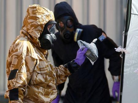 FILE PHOTO: Forensic investigators, wearing protective suits, emerge from the rear of John Baker House, after it was confirmed that two people had been poisoned with the nerve-agent Novichok, in Amesbury