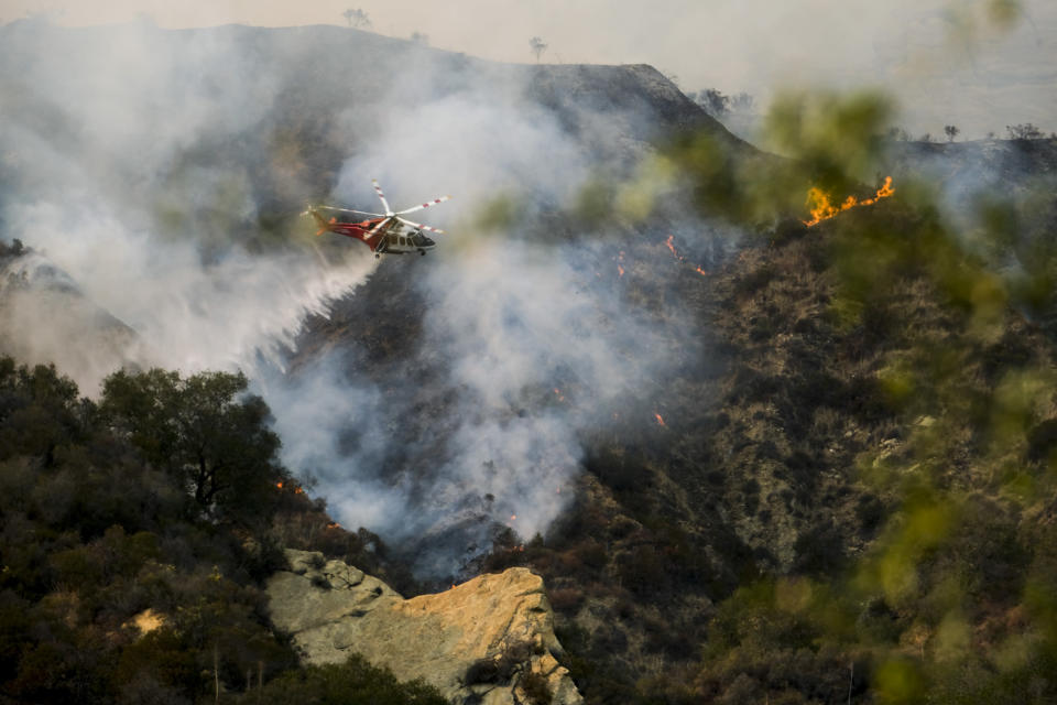 A firefighting helicopter drops water on a brush fire scorching at least 100 acres in the Pacific Palisades area of Los Angeles Saturday, May 15, 2021. (AP Photo/Ringo H.W. Chiu)