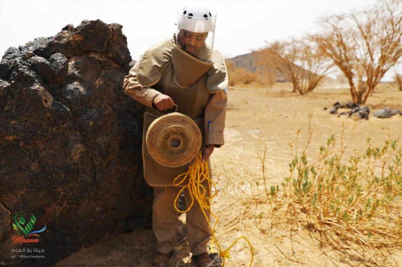 In this undated photograph released Aug. 19, 2018 by the state-run Emirates News Agency (WAM) on behalf of the Saudi-funded Masam anti-mine operation, an unidentified de-miner holds a deactivated mine near Marib, Yemen. Land mines scattered by Yemen's Houthi rebels will remain a threat even if the latest negotiations succeed in halting the civil war. While the Houthis' firing of ballistic missiles deep into Saudi Arabia has drawn the most attention, their widespread use of mines within Yemen represents a risk for generations to come in the Arab world's poorest country. Yemen is also littered with unexploded cluster munitions and bombs dropped by the Saudi-led coalition, including some made in the United States. (WAM via AP)