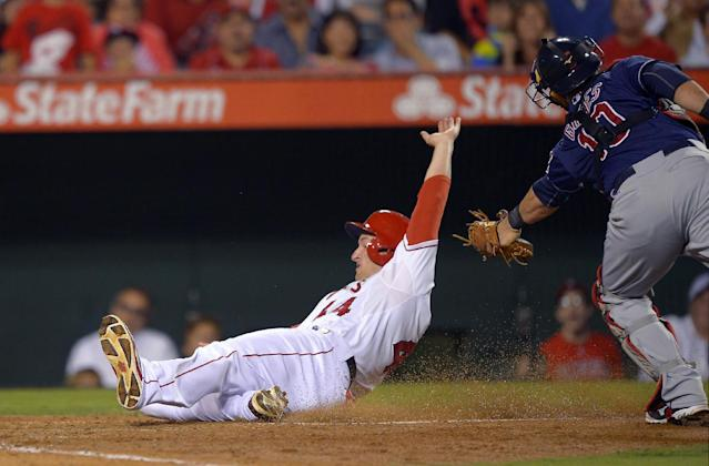 Los Angeles Angels' Mark Trumbo, left, is tagged out at home by Cleveland Indians catcher Yan Gomes as he tried to score on a fly ball by Chris Nelson during the fourth inning of their baseball game, Monday, Aug. 19, 2013, in Anaheim, Calif. (AP Photo/Mark J. Terrill)