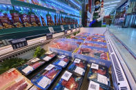 A worker wearing a mask and gloves stand near beef products from New Zealand packaged with a QR-code linked to its coronavirus test results displayed at a supermarket in Beijing, Tuesday, Nov. 24, 2020. China has stirred controversy with claims it has detected the coronavirus on packages of imported frozen food. (AP Photo/Ng Han Guan)