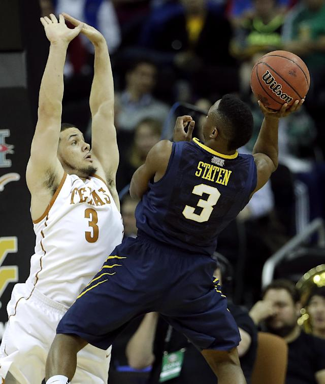 West Virginia's Juwan Staten, right, shoots under pressure from Texas' Javan Felix, left, during the first half of an NCAA college basketball game in the Big 12 men's tournament on Thursday, March 13, 2014, in Kansas City, Mo. (AP Photo/Charlie Riedel)