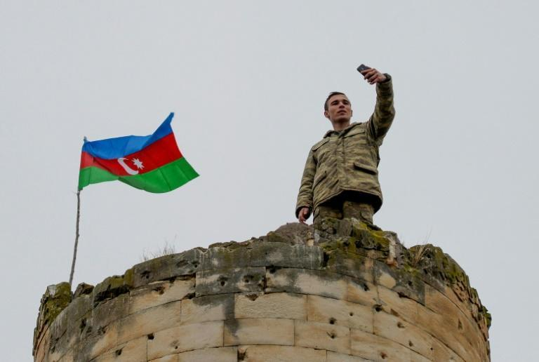 An Azerbaijan soldier takes a selfie with a national flag on the top a tower outside the town of Fuzuli