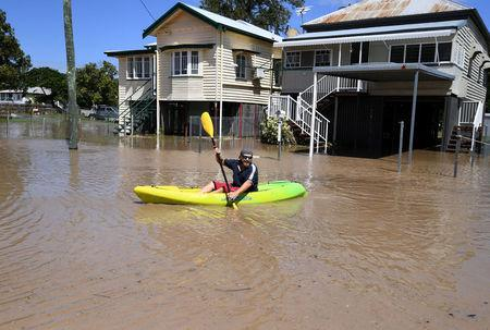 A local resident paddles his kayak through floodwaters in the wake of Cyclone Debbie in the suburb of Depot Hill in Rockhampton