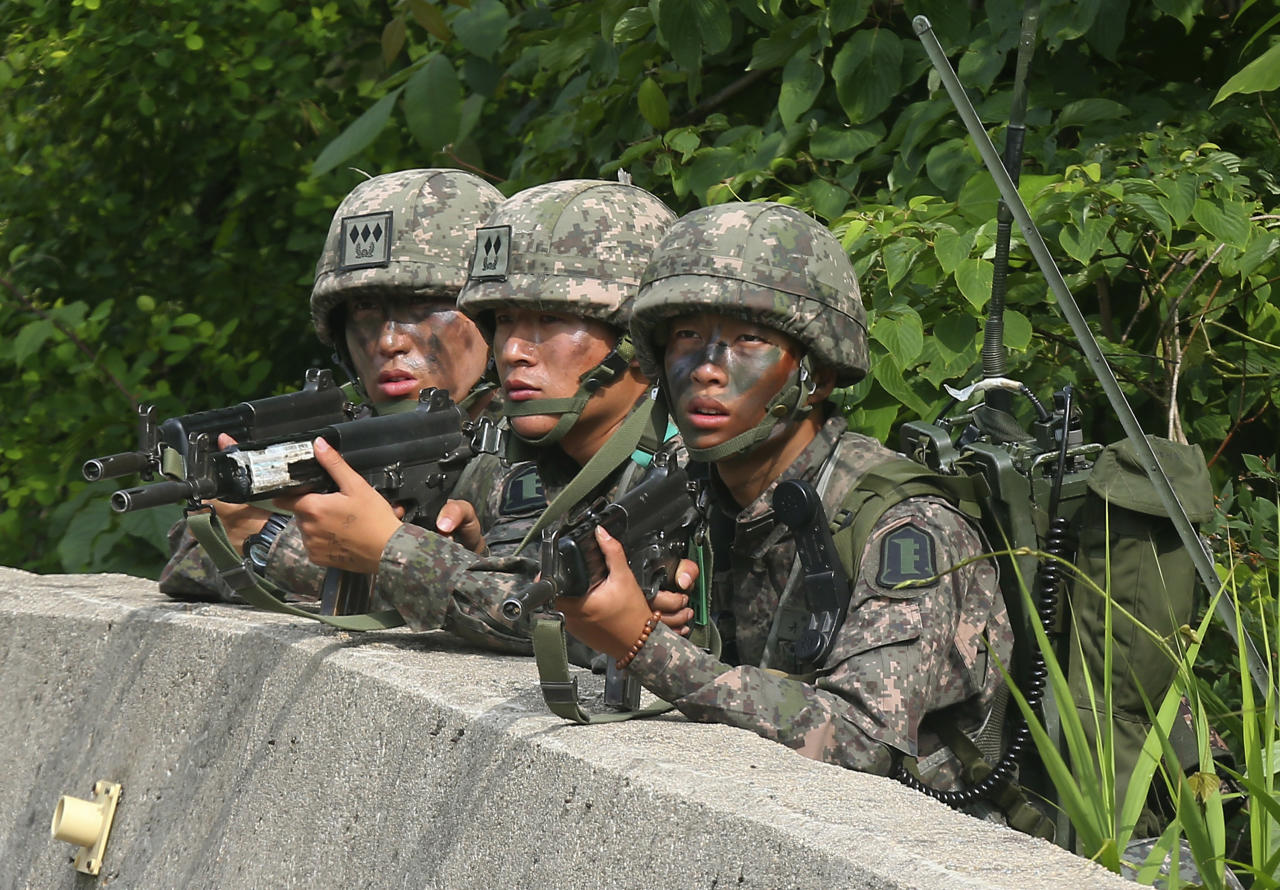 South Korean army soldiers aim their machine guns during an arrest operation in Goseong, South Korea, Monday, June 23, 2014. The parents of a runaway South Korean soldier suspected of killing five comrades at an outpost near the tense border with North Korea pleaded with him to surrender Monday as the military were besieging him and trying to capture him alive, officials said. (AP Photo/Yonhap, Hwang Kwang-mo) KOREA OUT