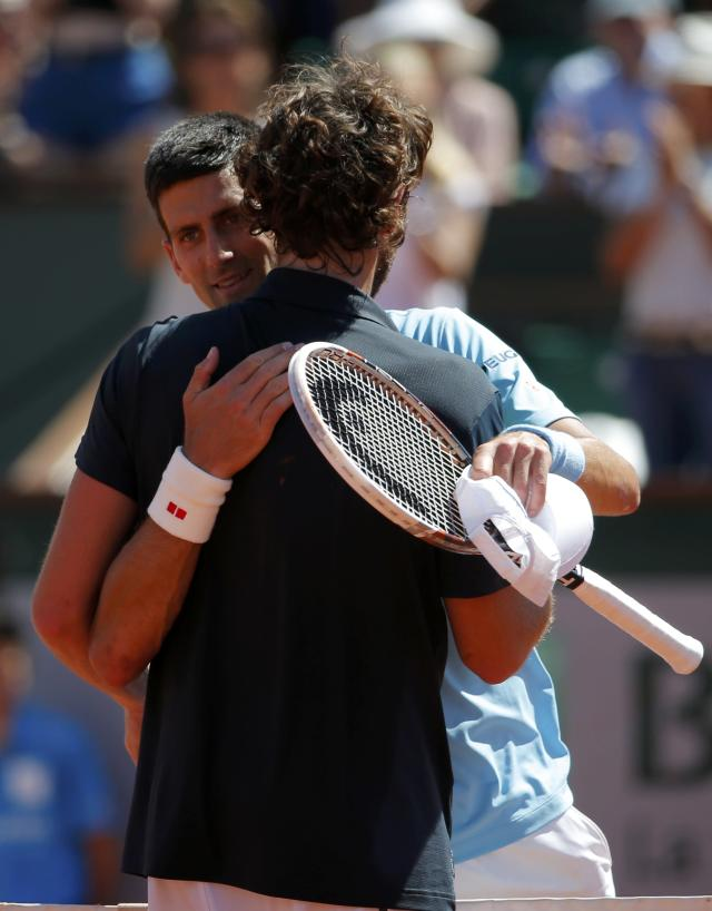 Novak Djokovic of Serbia (L) hugs Ernests Gulbis of Latvia after winning their men's semi-final match during the French Open tennis tournament at the Roland Garros stadium in Paris June 6, 2014. REUTERS/Gonzalo Fuentes (FRANCE - Tags: SPORT TENNIS)