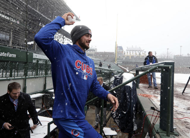 Chicago Cubs third baseman Kris Bryant emerges from the dugout with a snowball at Wrigley Field in Chicago, Monday, April 9, 2018. The Cubs baseball game against the Pittsburgh Pirates was postponed a day because of snow that covered much of Wrigley Field, creating a scene more reminiscent of January than April. (Brian Cassella/Chicago Tribune via AP)