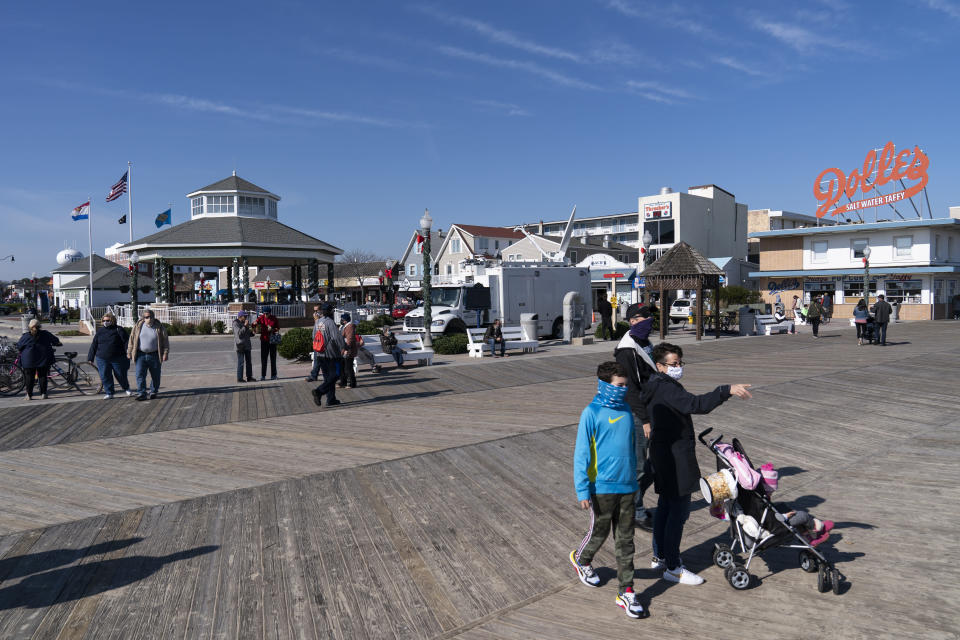 """People enjoy the boardwalk, Friday, Nov. 13, 2020, in Rehoboth Beach, Del. This resort town known for Atlantic waves that are sometimes surfable, fresh-cut French fries and a 1-mile wooden boardwalk that dates back to the 1870s has long prided itself on being the """"Nation's Summer Capital."""" (AP Photo/Alex Brandon)"""