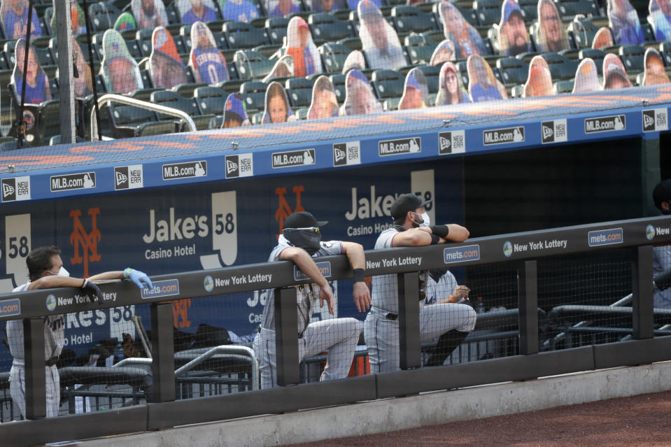 Miami Marlins players, protected against coronavirus in various ways, watch from the dugout during the seventh inning of a baseball game against the New York Mets at Citi Field, Sunday, Aug. 9, 2020, in New York. (AP Photo/Kathy Willens)