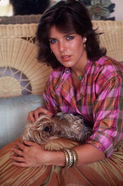 """<p>Princess Caroline posed for legendary photographer Slim Aarons in 1981 in pink plaid, <a href=""""https://www.townandcountrymag.com/style/jewelry-and-watches/a36100206/roberto-coin-gold-hoops-review/"""" rel=""""nofollow noopener"""" target=""""_blank"""" data-ylk=""""slk:gold hoops"""" class=""""link rapid-noclick-resp"""">gold hoops</a>, and bangles. On her lap: her pet dog Tiffany.</p>"""