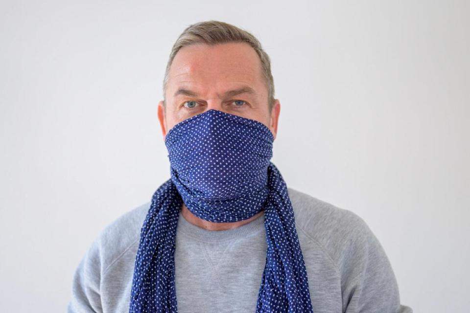 older wearing scarf as face covering