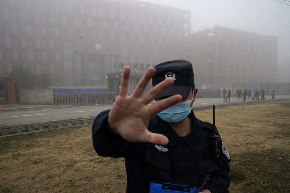 A security guard tries to cover a camera outside the Wuhan Institute of Virology.