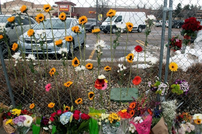 Flowers hang from the perimeter fence outside a King Soopers grocery store in Boulder, Colorado in March 2021, one day after a mass shooting that left ten people dead
