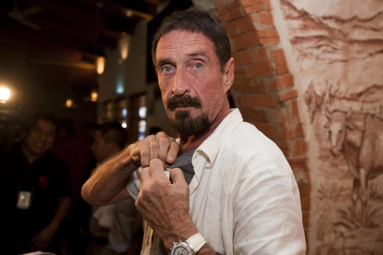 "Software company founder John McAfee adjusts a microphone in preparation for an interview in Guatemala City, Tuesday, Dec. 4, 2012. McAfee, 67, has been identified as a ""person of interest"" in the killing of his neighbor in Belize, 52-year-old Gregory Faull. Police are urging McAfee to come in for questioning. The anti-virus company founder fled Belize and is seeking political asylum in Guatemala, according to his lawyer Telesforo Guerra. (AP Photo/Moises Castillo)"