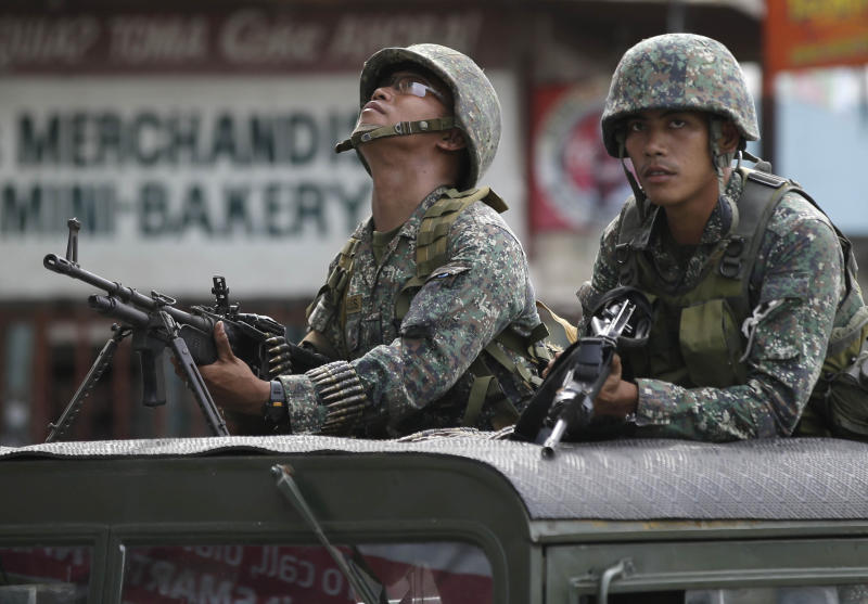 Government troopers inspect the surroundings during the continuing standoff with Muslim rebels, Sunday Sept. 15, 2013 in Zamboanga city, southern Philippines. The standoff, which began Monday when about 200 Moro National Liberation Front guerrillas stormed several coastal communities in Zamboanga city and seized several residents, has displaced more than 60,000, forced the closure of businesses and resulted in more than 50 deaths so far.(AP Photo/Bullit Marquez)